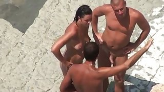 Some wettish take care besmeared FFM threesome breaks out on a beach